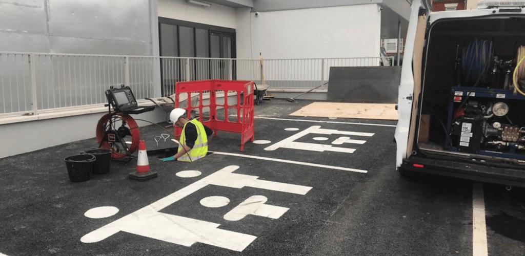 Man unblocking drain in Liverpool